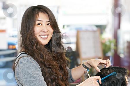 Hairstylist working stock photo, Happy hairdresser cutting hair in her salon by Elena Elisseeva