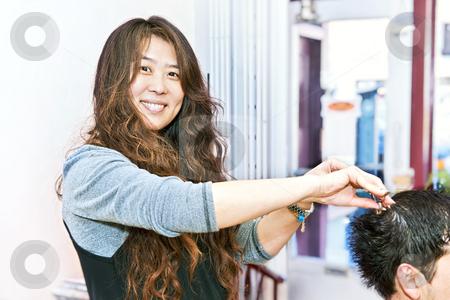 Hair stylist working stock photo, Happy hairstylist cutting hair in her salon by Elena Elisseeva
