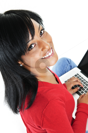 Young black woman using laptop computer stock photo, Smiling black woman looking up and typing on computer by Elena Elisseeva