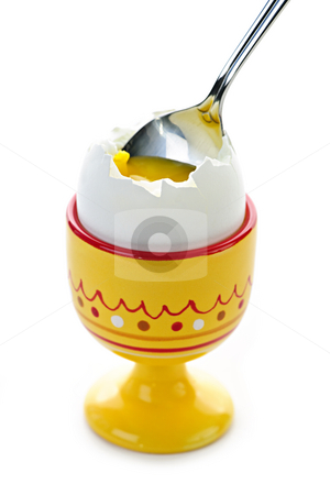 Soft boiled egg in cup stock photo, Closeup of soft boiled egg in cup with spoon on white background by Elena Elisseeva