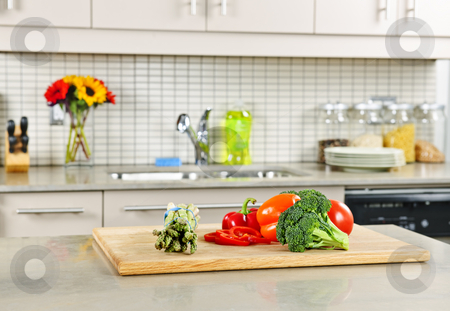 Kitchen interior stock photo, Modern kitchen interior with fresh vegetables on natural stone countertop by Elena Elisseeva