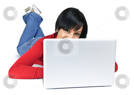 Young woman with laptop computer stock photo, Smiling black woman peeking from behind computer laying on floor by Elena Elisseeva