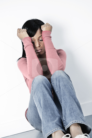 Depressed woman sitting on floor stock photo, Depressed black woman sitting against wall on floor with eyes closed by Elena Elisseeva