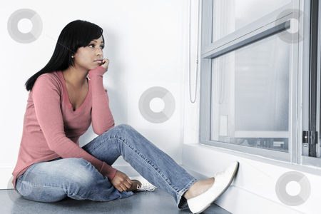 Depressed woman sitting on floor stock photo, Depressed black woman sitting against wall on floor looking out window by Elena Elisseeva
