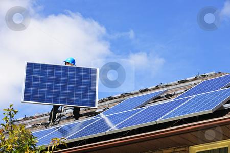 Solar panel installation stock photo, Worker installing alternative energy photovoltaic solar panels on roof by Elena Elisseeva