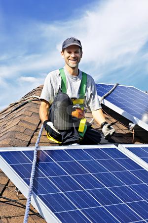 Solar panel installation stock photo, Man installing alternative energy photovoltaic solar panels on roof by Elena Elisseeva