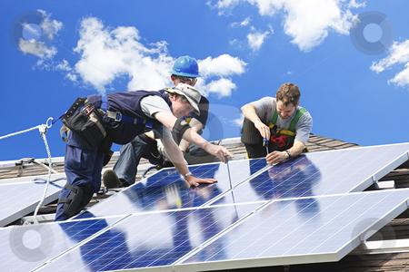 Solar panel installation stock photo, Workers installing alternative energy photovoltaic solar panels on roof by Elena Elisseeva