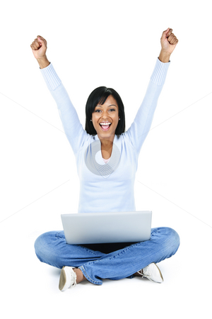 Successful young woman with computer stock photo, Happy black woman with arms raised and computer isolated on white background by Elena Elisseeva