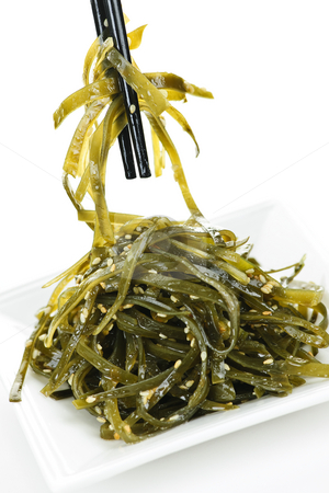Seaweed salad stock photo, Plate of wakame seaweed salad with chopsticks on white background by Elena Elisseeva