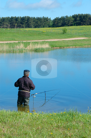 Fisherman stock photo, A fisherman with a fishing rod in the water near the shore of Lake by Vladimir Blinov