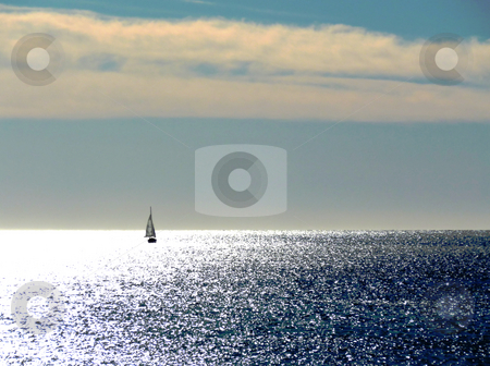 Sailing boat stock photo, Small sailing boat on the mediterranean sea enlightened and pink clouds by Elenarts
