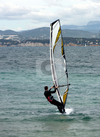 Windsurfer by cold weather stock photo, Suited windsurfer on mediterranean french coastline by cold weather by Elenarts