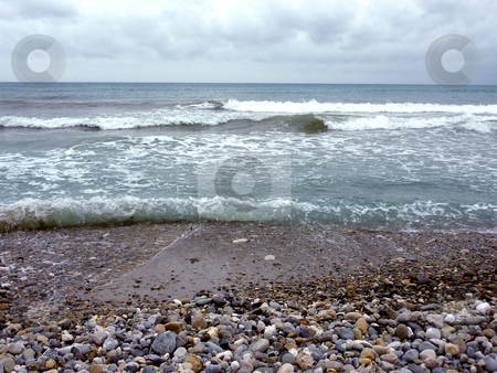 Beach and waves stock photo, Mediterranean sea and its waves at a beach with lots of pebbles and small brown and grey stone, by cloudy weather by Elenarts