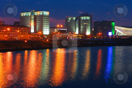 City late in the evening stock photo, City late in the evening, lights reflected in the river water. by Vladimir Blinov