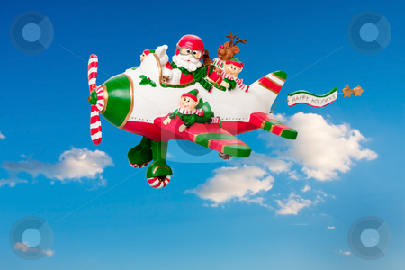 Flying Santa Claus with Elves in Airplane stock photo, Santa Claus flying his airplane with Happy Holidays banner in the sky with his elves and Rudolf the Red nosed Reindeer. by Paul Hakimata