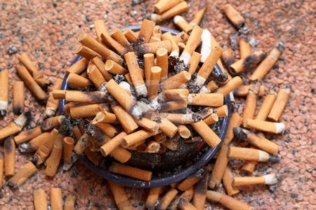 Ashtray full of cigarettes close-up stock photo, Ashtray full of cigarettes close-up by Artush