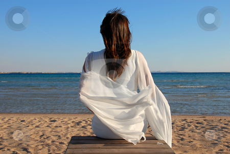 Woman sitting on beach stock photo, Woman in white dress back sitting on beach by sea by Julija Sapic