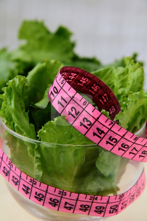 Green salad diet with a pink measuring tape stock photo,  by Olga Kriger