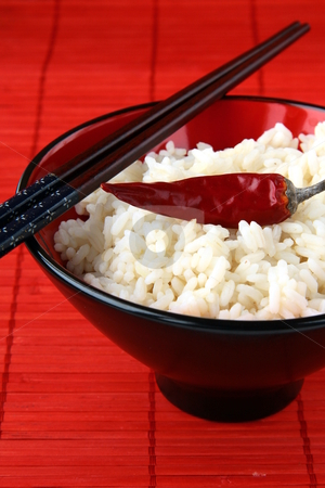 White rice in a bowl with black chopsticks on a red background  stock photo,  by Olga Kriger