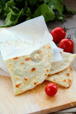 Indian  nan bread on a wooden board stock photo,  by Olga Kriger