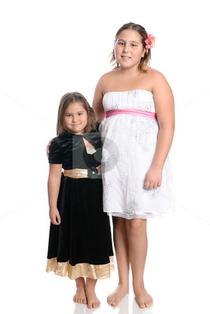 Sisters Isolated On White stock photo, Two young sisters smiling and wearing pretty dresses are isolated on a white background. by Richard Nelson