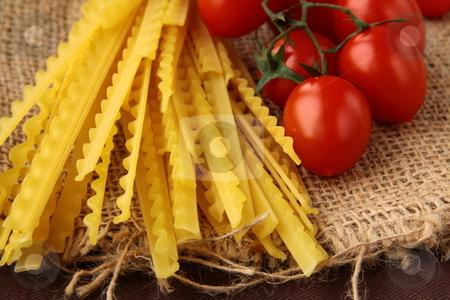Italian pasta on a wooden board wish tomato stock photo,  by Olga Kriger