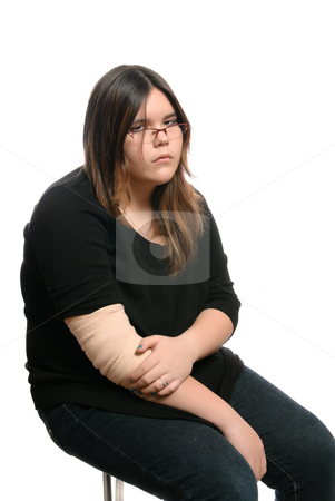 Teenage Elbow Injury stock photo, A bored teenage girl is tired of having an injured elbow, and is sitting on a stool, isolated against a white background. by Richard Nelson