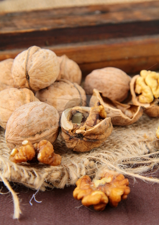 Whole and chopped walnuts on a brown background stock photo,  by Olga Kriger