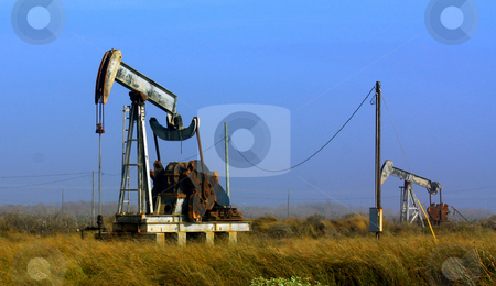 Oil Rig in Fog stock photo, Rig pumping oil while fog rolls in across the grasslands in winds up to 20mph. by Marburg