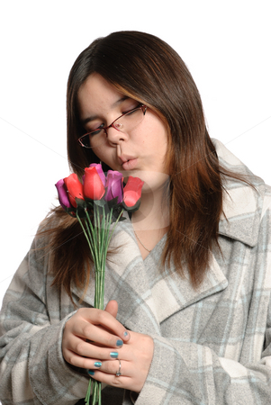 Teen Holding Roses stock photo, A brunette teen is holding multicolored wooden roses, isolated against a white background. by Richard Nelson