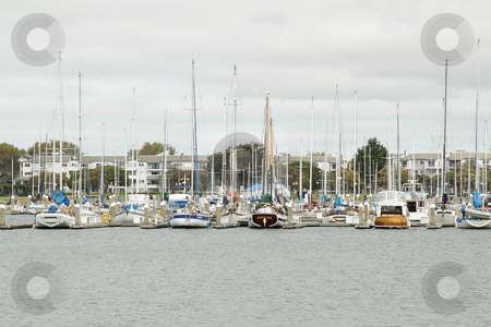 Yachts on pier stock photo, Row of yachts on pier on overcast day by Olena Pupirina