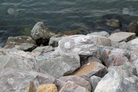 Stones by the water stock photo, Stones near the water on cloudy day by Olena Pupirina