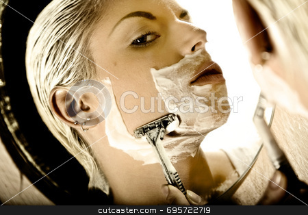 Androgeny stock photo, Woman shaving her face with a razor by Luca Mosconi