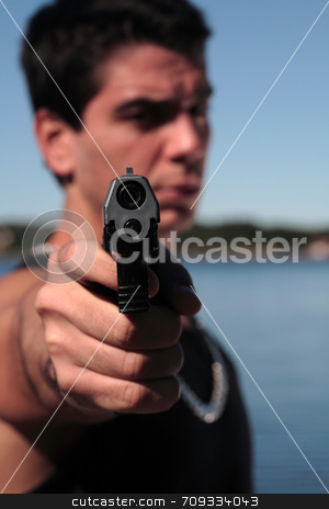 Armed 3 stock photo, A young man, wearing a sleeveless shirt, holding a hand gun. (This image is part of a series) by Daniel Wiedemann