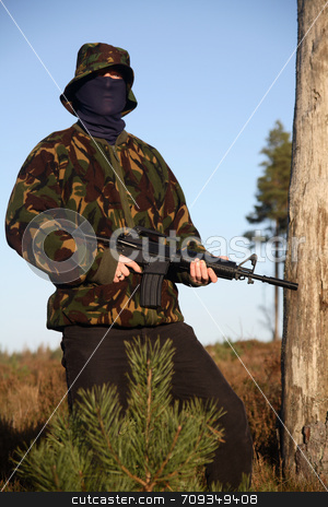 Soldier with Camouflage (standing) stock photo, A soldier holding a M16 (AR-15) Rifle with camouflage and a balaclava. by Daniel Wiedemann