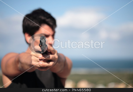 Shooter stock photo, A young, robust man, in his 20's with dark hair pointing 2 pistols to the camera. by Daniel Wiedemann