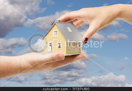 Reaching For A Home stock photo, Female hand reaching for a house on a partly cloudy sky background. by Andy Dean