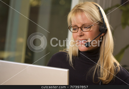 Attractive Businesswoman with Phone Headset stock photo, Attractive businesswoman talks on her phone headset. by Andy Dean