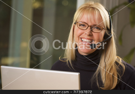 Attractive Businesswoman with Phone Headset stock photo, Attractive businesswoman smiles as she talks on her phone headset. by Andy Dean