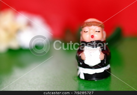 Little Monk stock photo, A toy monk in front of a red and green background by Henrik Lehnerer