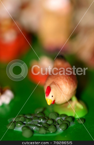 Little Chicken stock photo, A little colorful toy chicken that is eating some corn by Henrik Lehnerer