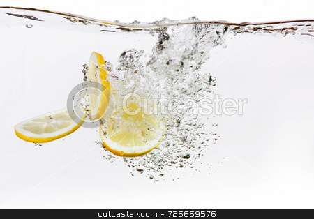 Lemon Slice Water Drop stock photo, A group of lemon slices dropped in water with bubbles by Tyler Olson