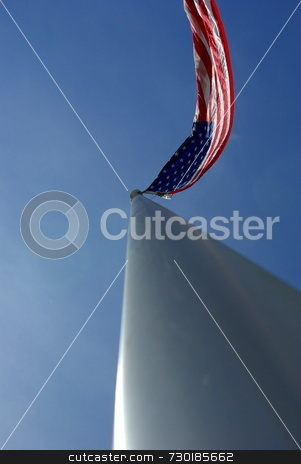 American Flag On An Aluminum Flagpole stock photo, A unique view of a large American flag flying from the top of an aluminim flagpole. by Lynn Bendickson