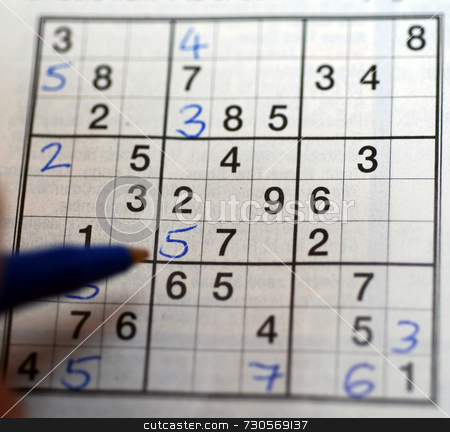 Playing Sudoku stock photo, A left-handed person solving a Sudoku puzzle by Philippa Willitts