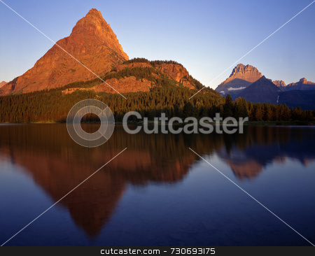 Swiftcurrent Lake Morning stock photo, Mountains reflecting in Swiftcurrent Lake located in Glacier National Park, Montana, photographed in the early morning. by Mike Norton