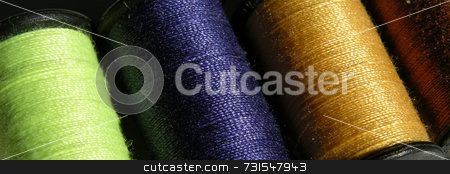 Threads stock photo, Four spools of thread seen closeup in different colors by Tim Markley