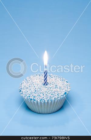 Blue cupcake with white sprinkles stock photo, A blue cupcake with white sprinkles and a candle by Jon Stokes