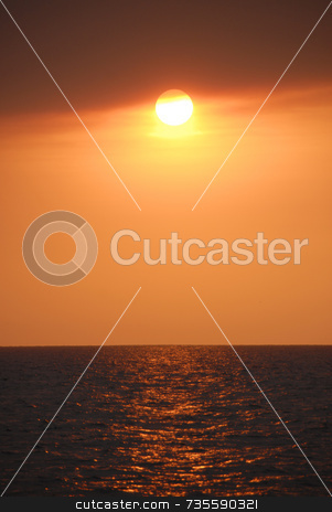 Fire Sunset over Ocean stock photo, Orange sun over ocean by A Cotton Photo
