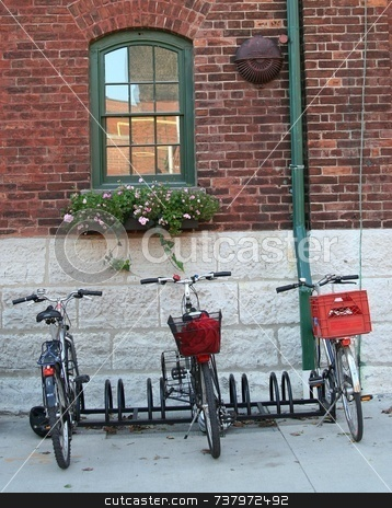 Three Bicycles parked by a brick wall stock photo, Three bicycles, two with red luggage carriers parked by old-fashioned brick wall with window with green paint and flower box. by Wes Shepherd