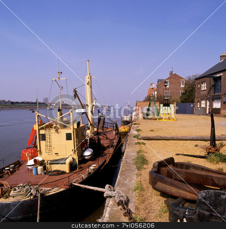Dock stock photo, An old working boat tied up at low tide for repair by Paul Phillips